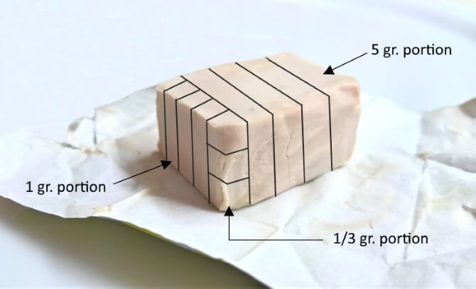 A 25 gr. cube of fresh yeast, sectioned to obtain the necessary amount for 4 pizzas.